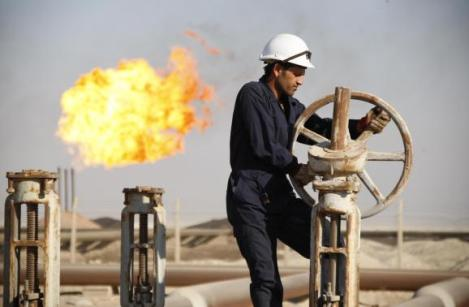 File photo of a worker adjusting the valve of an oil pipe at West Qurna oilfield in Iraq's southern province of Basra